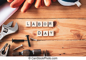 USA Labor day concept, First Monday in September. Different kinds on wrenches, handy tools, America flag and wooden blocks on wooden table.