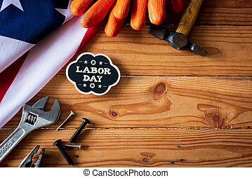 USA Labor day concept, First Monday in September. Different kinds on wrenches, handy tools, America flag and wooden tag on wooden table.