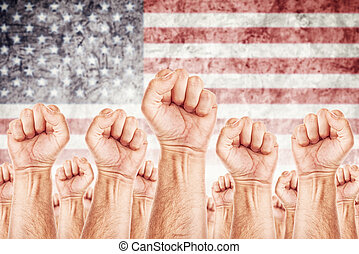 United States of America Labour movement, workers union strike concept with male fists raised in the air fighting for their rights, American national flag in out of focus background.