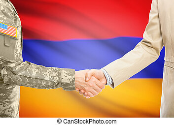 USA military man in uniform and civil man in suit shaking hands with national flag on background - Armenia