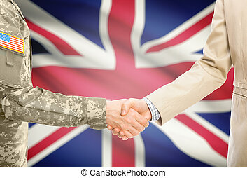 USA military man in uniform and civil man in suit shaking hands with national flag on background - United Kingdom