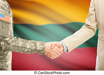 USA military man in uniform and civil man in suit shaking hands with national flag on background - Lithuania