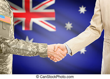 USA military man in uniform and civil man in suit shaking hands with national flag on background - Australia