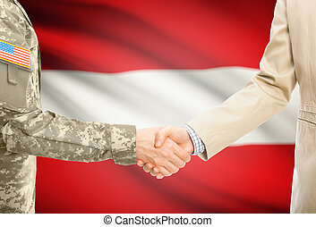 USA military man in uniform and civil man in suit shaking hands with national flag on background - Austria