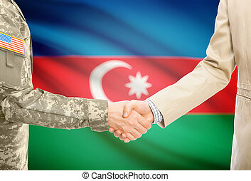 USA military man in uniform and civil man in suit shaking hands with national flag on background - Azerbaijan