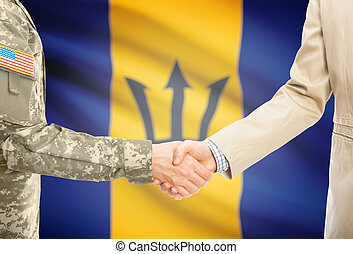 USA military man in uniform and civil man in suit shaking hands with national flag on background - Barbados