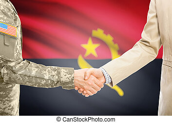 USA military man in uniform and civil man in suit shaking hands with national flag on background - Angola