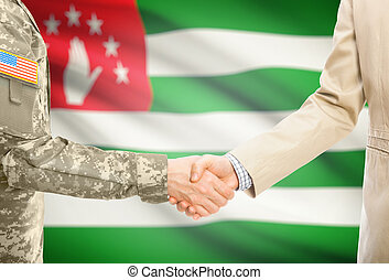 USA military man in uniform and civil man in suit shaking hands with national flag on background - Abkhazia