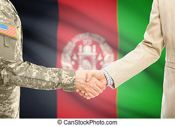 USA military man in uniform and civil man in suit shaking hands with national flag on background - Afghanistan