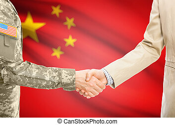 USA military man in uniform and civil man in suit shaking hands with national flag on background - China