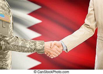 USA military man in uniform and civil man in suit shaking hands with national flag on background - Bahrain