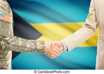 USA military man in uniform and civil man in suit shaking hands with national flag on background - Bahamas