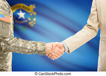 American soldier in uniform and civil man in suit shaking hands with USA state flag on background - Nevada