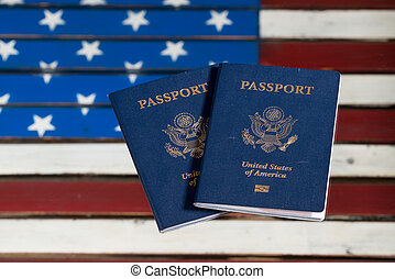 USA passports on glass table over US Flag - Pair of USA...