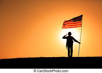 USA Soldier with flag saluting on sunset horizon
