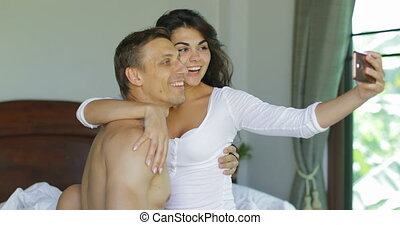 usage, amants, photo, couple, chambre à coucher, jeune, lit, téléphone portable, femme, intelligent, embrasser, prendre, heureux, selfie, baisers, homme