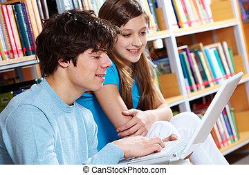 usando computador portátil, biblioteca