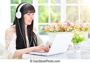 usando computador portátil, mulher, fones