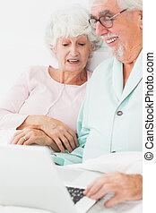 usando computador portátil, par, sorrindo, cama