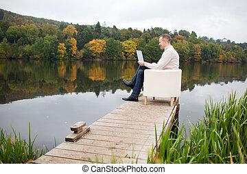usar la computadora portátil, al aire libre, hombre maduro