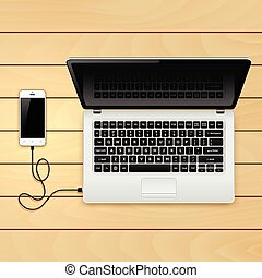 USB cable connect phone and laptop on the wooden table....