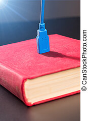 Usb cable plugged into a book