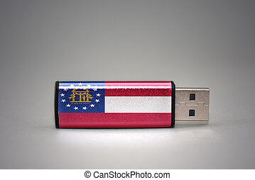 usb flash drive with the georgia state flag on gray background.