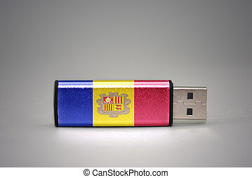 usb flash drive with the national flag of andorra on gray background.