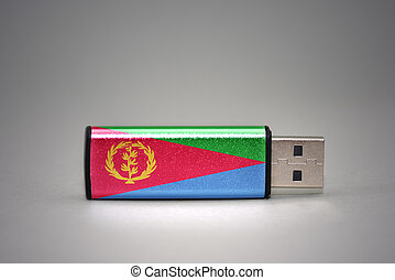 usb flash drive with the national flag of eritrea on gray background.