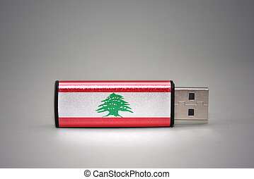 usb flash drive with the national flag of lebanon on gray background.