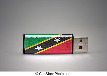 usb flash drive with the national flag of saint kitts and nevis on gray background.