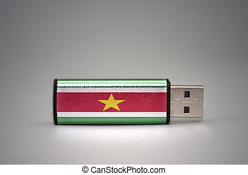 usb flash drive with the national flag of suriname on gray background.