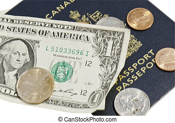 Canadian loonie on top of the USD with a clipping path aslo a canadian passport with clipping path.
