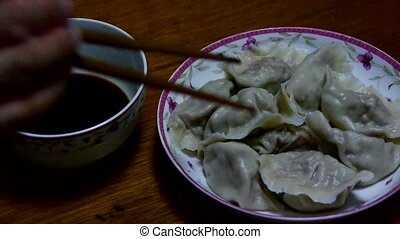 use chopsticks eating dumplings,tradition chinese new year...