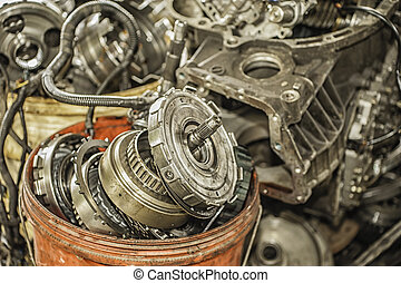 Bucket of used and worn out automobile parts.