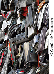 Used car bumpers are stacked neatly at a used car parts dealer