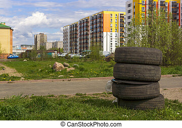 Used car tires on a lawn on background of cityscape in summer