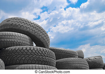 Old car tyres and cloudy blue sky