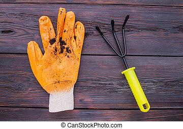 Used dirty gardening glove and three-jaw rake fork.