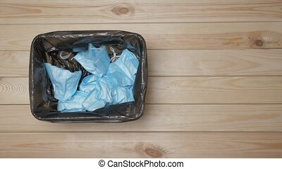 Used Masks Throwaway in Trash Bin. Trash can with Medical Masks. Disposing medical waste. Throw Away Used Mask. Medical Mask After Use. Separating Infected Waste. Top View. Garbage Bucket with Masks