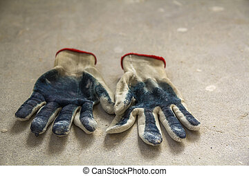 Used old dirty torn worker's gloves as a metaphor, concept or symbol for the end of the work season