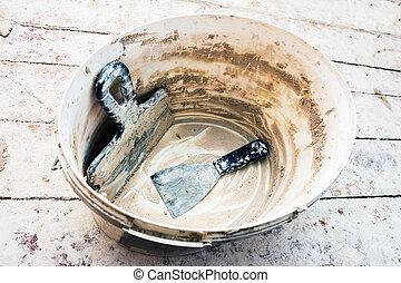 Used spatulas in a bucket