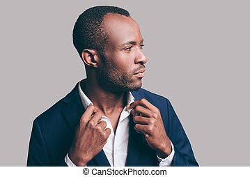 Used to look perfect. Portrait of confident young African man adjusting his shirt collar and looking away while standing against grey background