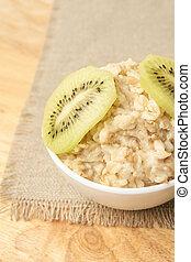 Useful breakfast. Oatmeal with kiwi. Neutral background