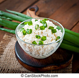 Useful cottage cheese with chives in a glass bowl on a ...