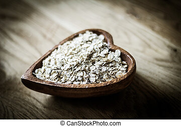 useful oat flakes in a wooden bowl