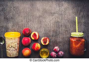 Useful peach fruit smoothie in glass bottle and straws and oatmeal with fruits, vegetarian breakfasts