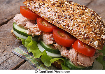 Useful tuna sandwich with lettuce, tomatoes, cucumbers close...