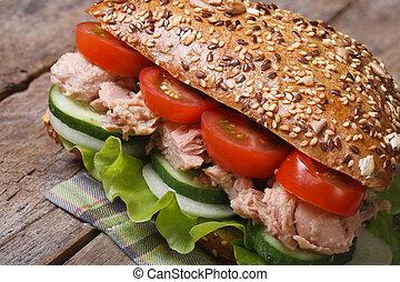 Useful tuna sandwich with lettuce, tomatoes, cucumbers close...