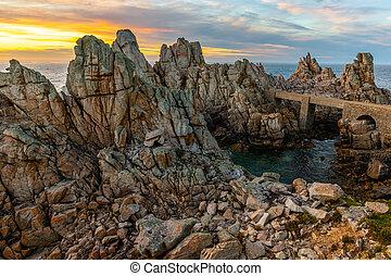 The sharp rocky coastline of Ushant island at sunset, Brittany, France